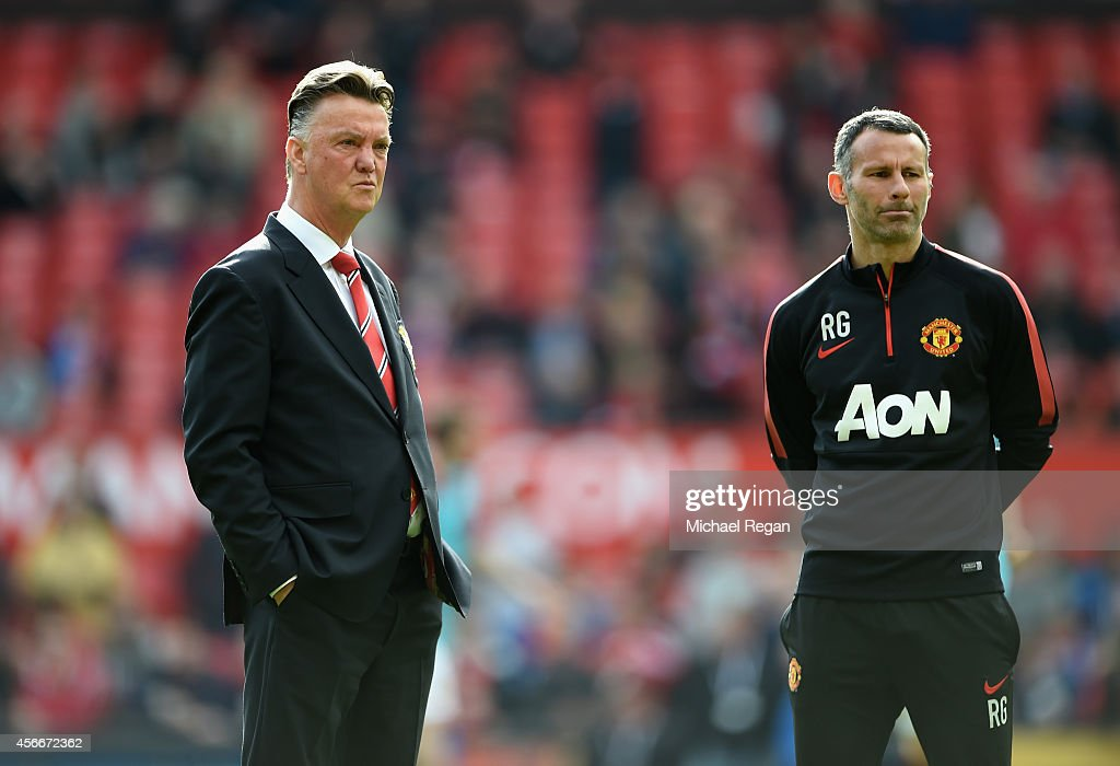 Manchester United Manager Louis van Gaal (L)looks on with Assistant Ryan Giggs prior to the Barclays Premier League match between Manchester United and Everton at Old Trafford on October 5, 2014 in Manchester, England.