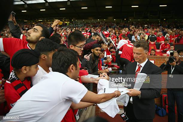 Manchester United manager Louis Van Gaal signs autographs as he makes his home debut during the Pre Season Friendly match between Manchester United...