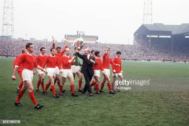 Manchester United manager Matt Busby holds the League Championship trophy aloft as he and his players parade it around Old Trafford Denis Law Bill...