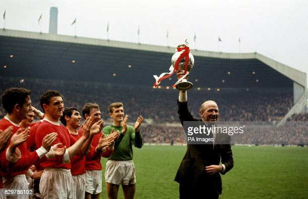 Manchester United manager Matt Busby holds the League Championship trophy aloft as his players applaud Shay Brennan Bill Foulkes Tony Dunne Pat...