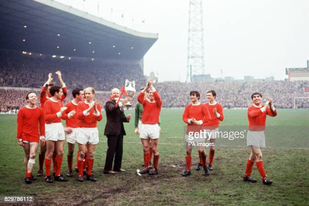 Manchester United manager Matt Busby holds the League Championship trophy aloft as he and his players parade it around Old Trafford Nobby Stiles...