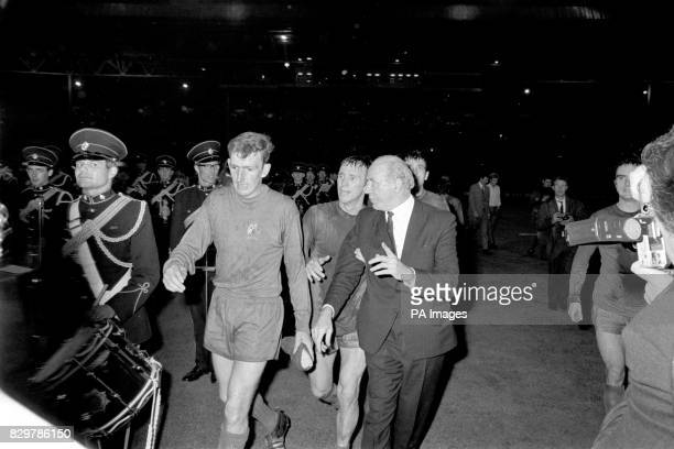 Manchester United manager Matt Busby is escorted off the pitch by Alex Stepney and Pat Crerand after United's 41 win