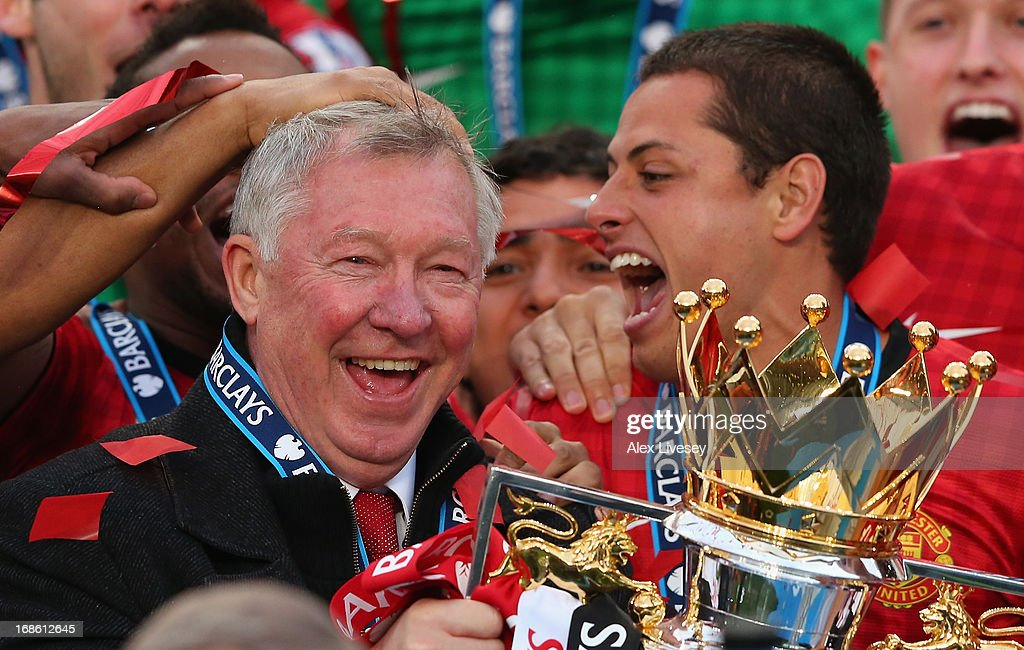 Manchester United Manager Sir Alex Ferguson celebrates with his players and the Premier League trophy following the Barclays Premier League match between Manchester United and Swansea City at Old Trafford on May 12, 2013 in Manchester, England.