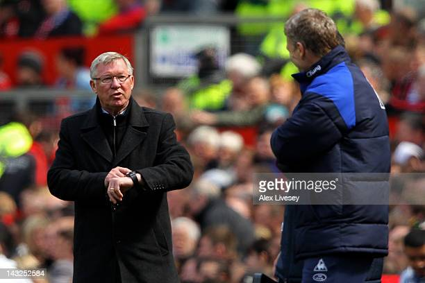 Manchester United Manager Sir Alex Ferguson gestures to his watch during the Barclays Premier League match between Manchester United and Everton at...