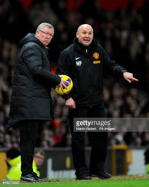 Manchester United manager Sir Alex Ferguson holds the match ball with assistant coach Mike Phelan during the Barclays Premier League match at Old...