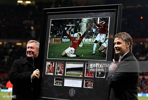 Manchester United Manager Sir Alex Ferguson presents Ole Gunnar Solskjaer with a print of his winning goal celebration from the 1999 Champions League...