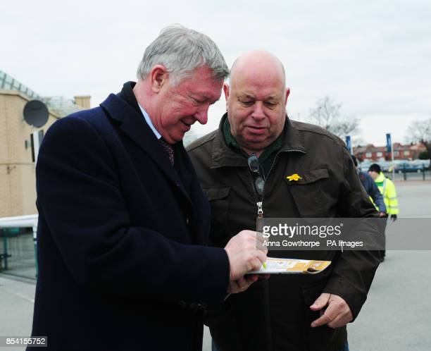 Manchester United manager Sir Alex Ferguson signs an autograph for a fan at Doncaster Racecourse
