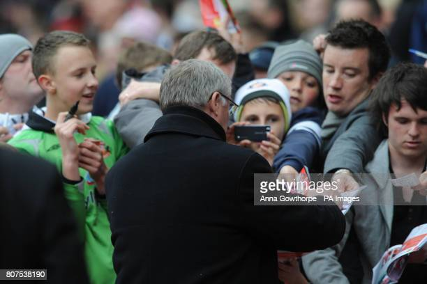 Manchester United manager Sir Alex Ferguson signs autographs for fans before kick off of the Barclays Premier League Match at the Stadium of Light...