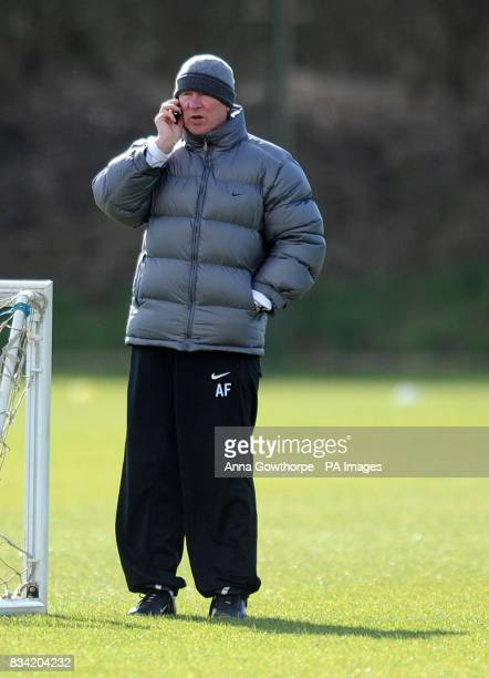 Manchester United manager Sir Alex Ferguson talks on his phone during a training session at Carrington Training Ground Manchester
