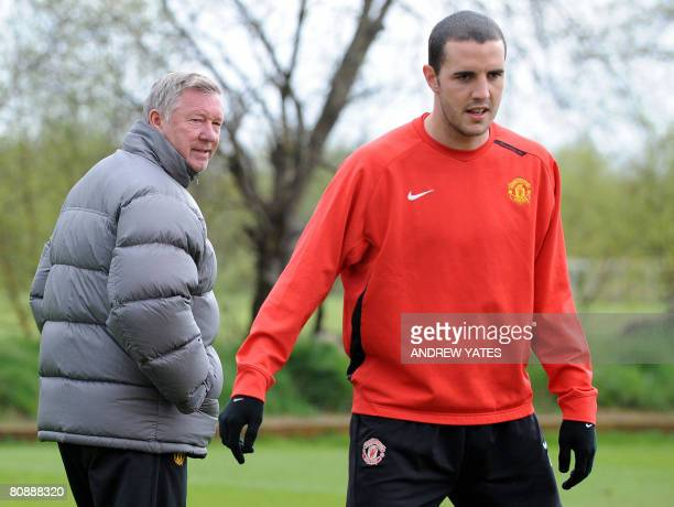 Manchester United manager Sir Alex Ferguson walks past Manchester United's Irish defender John O'Shea during a team training session at the...