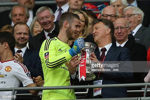 Manchester United Managr Louis van Gaal and David de Gea hold the trophy following their side's 12 victory as Sir Alex Ferguson and David Gill look...