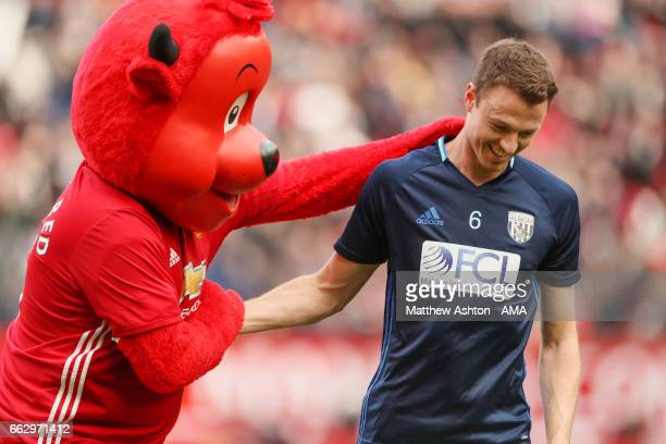 Manchester United mascot Fred The Red greets Jonny Evans of West Bromwich Albion prior to the Premier League match between Manchester United and West...