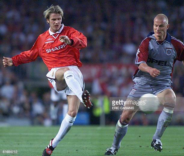 Manchester United midfielder David Beckham kicks the ball past Bayern Munich forward Carsten Jancker 26 May 1999 at the Camp Nou Stadium in Barcelona...