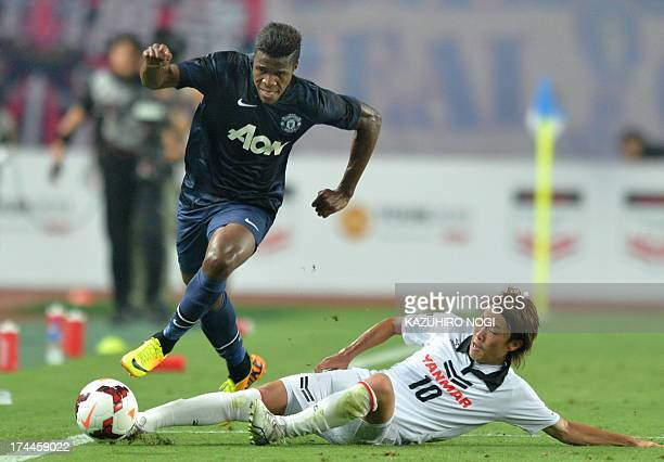 Manchester United midfielder Wilfried Zaha clears a sliding tackle by Cerezo Osaka midfielder Jumpei Kusukami during their friendly football match at...