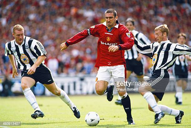 Manchester United player Eric Cantona beats Steve Watson and David Batty during the FA Charity Shield match between Manchester United and Newcastle...