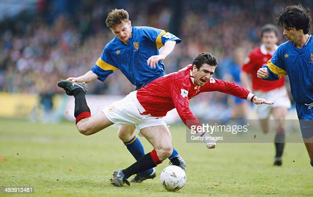 Manchester United player Eric Cantona is challenged by Brian MCallister during the FA Premier League Match between Wimbledon and Manchester United at...