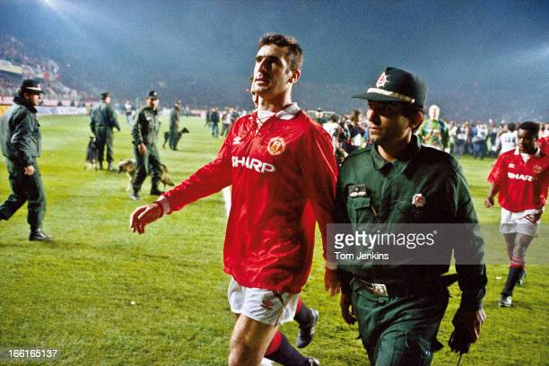 Manchester United player Eric Cantona is escorted from the pitch by a policeman after he was sent off at the end of the Champions League second round...