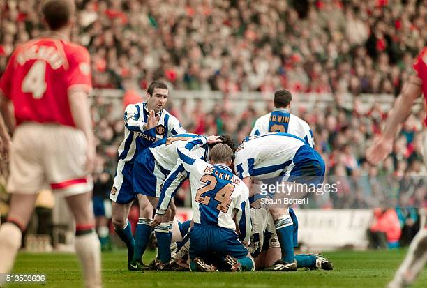 Manchester United player Eric Cantona joins in the celebrations with team mates after David May had scored the first goal in a 30 win to seal the...