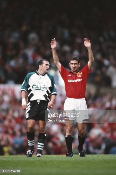 Manchester United player Eric Cantona reacts as Neil Ruddock of Liverpool looks on during a Premiership match on September 17 1994 in Manchester...