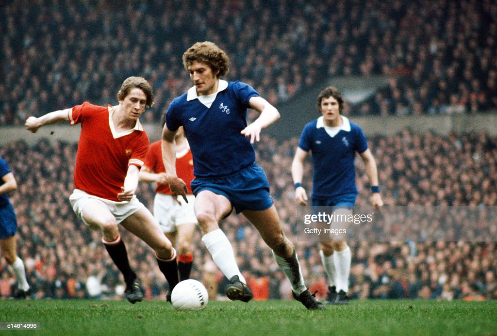 Manchester United player Gerry Daly (l) attempts to close down Everton midfielder Martin Dobson as centre half Mick Lyons sporting sweat bands (r) looks on during a League Division One match between Manchester United and Everton at Old Trafford on April 17, 1976 in Manchester, England.