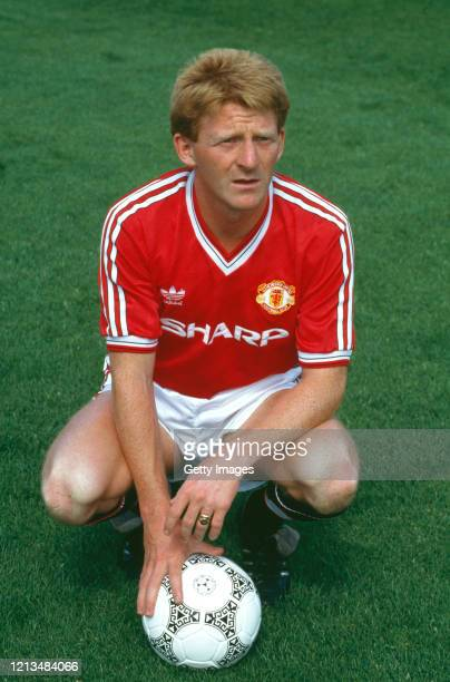 Manchester United player Gordon Strachan pictured kneeling with an Adidas match ball during the Squad photo call ahead of the 1987/88 season possibly...
