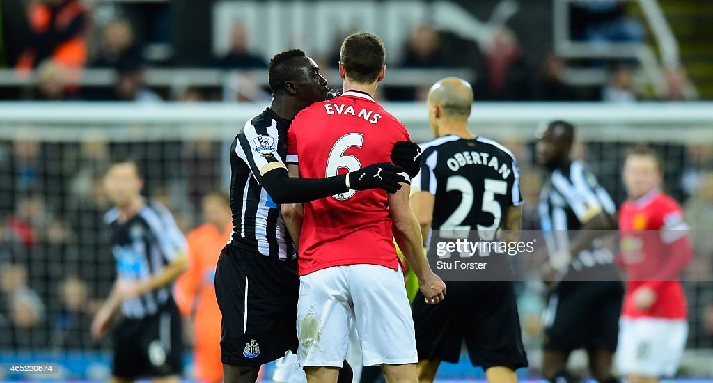 Manchester United player Jonny Evans (r) looks on as Papiss Cisse of Newcastle appears to spit during the Barclays Premier League match between Newcastle United and Manchester United at St James' Park on March 4, 2015 in Newcastle upon Tyne, England.