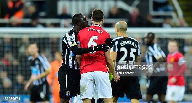 Manchester United player Jonny Evans looks on as Papiss Cisse of Newcastle appears to spit during the Barclays Premier League match between Newcastle...