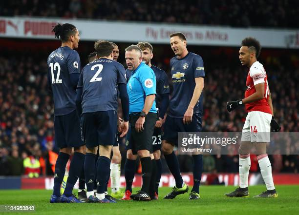 Manchester United players argue with referee Jonathon Moss after he awards Arsenal a penalty during the Premier League match between Arsenal FC and...