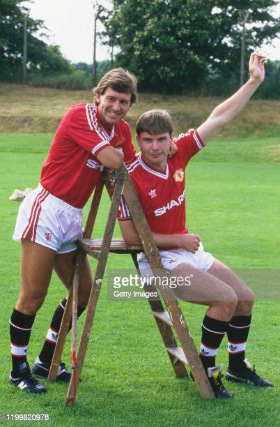 Manchester United players Bryan Robson and Brian McClair pictured on a set of step ladders during the Squad photo call ahead of the 1987/88 season,...