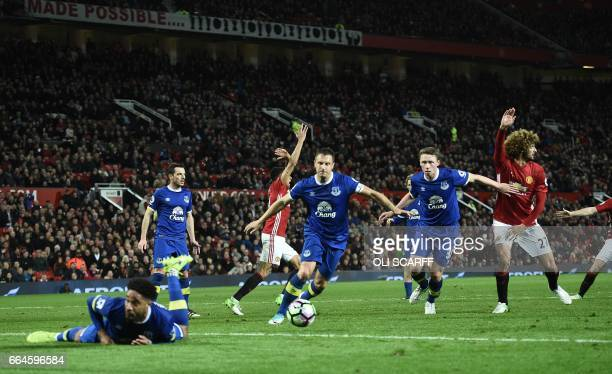 Manchester united players call for hand ball after Everton's Englishborn Welsh defender Ashley Williams stopped the ball in the penalty area during...