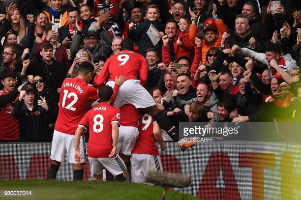 TOPSHOT Manchester United players celebrate after Manchester United's English striker Marcus Rashford scored the opening goal during the English...