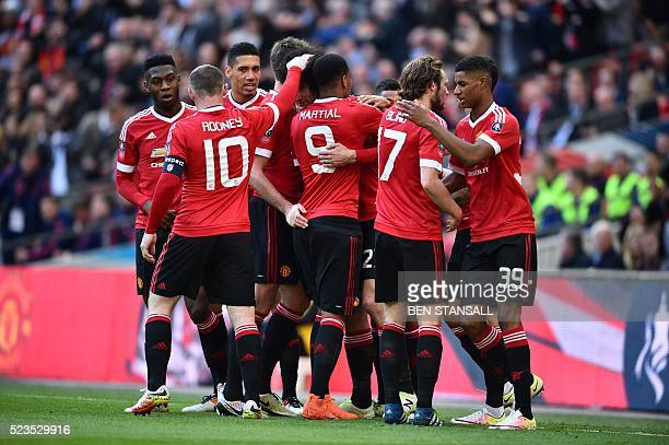 Manchester United players celebrate Manchester United's Belgian midfielder Marouane Fellaini after he scored the opening goal during the English FA...