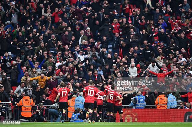 Manchester United players celebrate with the crowd after their French striker Anthony Martial scored their second goal during the English FA Cup...