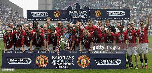Manchester United players celebrate with the Premier League trophy after beating Wigan Athletic in their English Premier League football match at The...