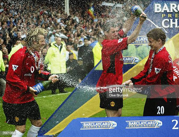 Manchester United players David Beckham Roy Keane and Ole Gunnar Solskjaer celebrate winning the league by spraying champagne at each other after the...
