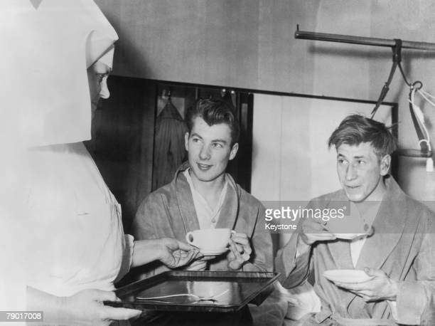 Manchester United players Ken Morgan left and Bobby Charlton receive hot soup from a nurse at the Isar Hospital in Munich where they are recovering...