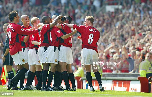 Manchester United players line up to celebrate with goal scorer Ryan Giggs after he scored the opening goal against Bolton Wanderers during the first...