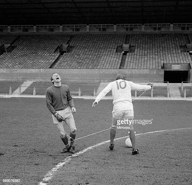 Manchester United players Nobby Stiles and Denis Law playing against each other during a training session at Old Trafford. The two players try to...