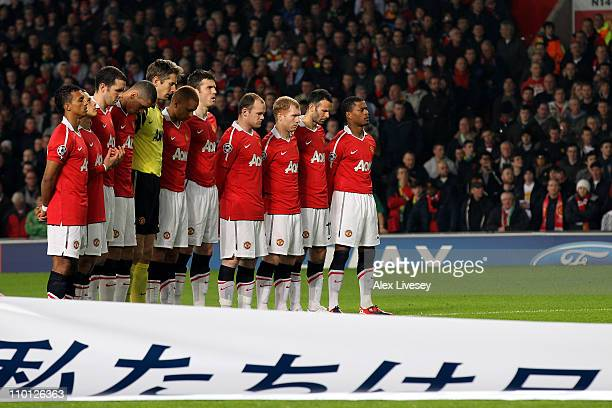 Manchester United players observe a minutes silence in memory of the Japanese earthquake victims ahead of the UEFA Champions League round of 16...