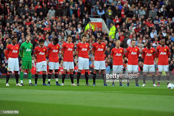 Manchester United players stand for a minutes silence in memory of Italian footballer Piermario Morosini ahead of an English Premier League football...