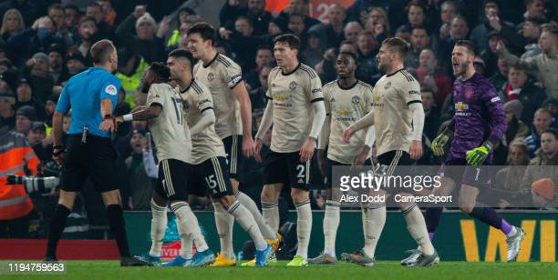 Manchester United players surround referee Craig Pawson during the Premier League match between Liverpool FC and Manchester United at Anfield on...