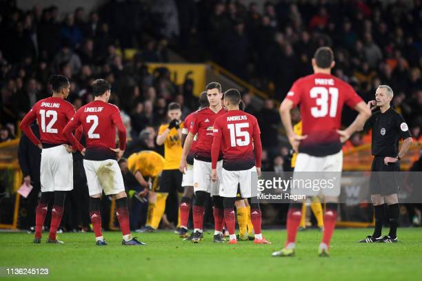 Manchester United players surround referee Martin Atkinson as he confers with the VAR on a red card decision for Victor Lindelof of Manchester United...