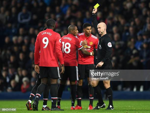 Manchester United players surrounded referee Anthony Taylor as Marcus Rashford of Manchester United is shown a yellow card during the Premier League...