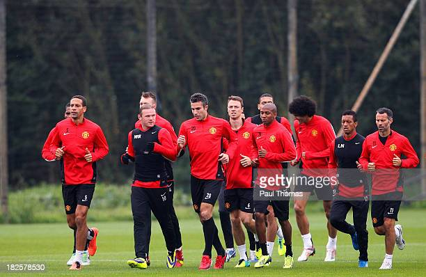 Manchester United players warm up during a training session ahead of their Champions League Group A match against Shakhtar Donetsk at their...