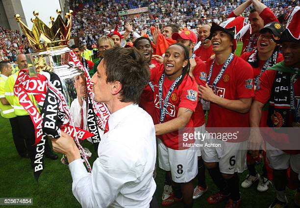 Manchester United players watch Gary Neville kiss the FA Barclays Premier League trophy after being champions and winning the league season 20072008