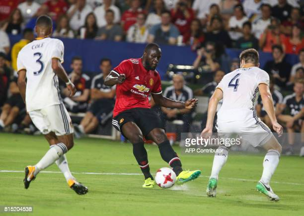 Manchester United Romelu Lukaku kicks the ball past Los Angeles Galaxy's Ashley Cole and Dave Romney during the second half of a national friendly...