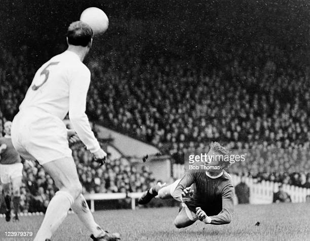 Manchester United striker Denis Law dives to head the ball watched by Leeds United defender Jack Charlton during the First Division match at Old...