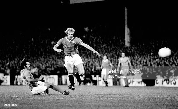 Manchester United striker Jimmy Greenhoff evades a St Etienne defender and shoots during the European Cup Winners Cup 1st round 2nd leg match played...