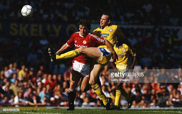 Manchester United striker Mark Hughes is challenged by Leeds defender John McClelland during a League Division One match at Old Trafford on August...