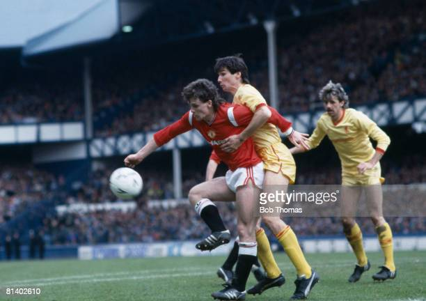 Manchester United striker Mark Hughes is tightly marked by Liverpool defender Alan Hansen with Mark Lawrenson looking on during their FA Cup...